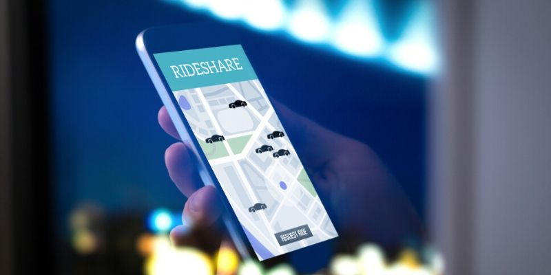 person holding phone with ride sharing app
