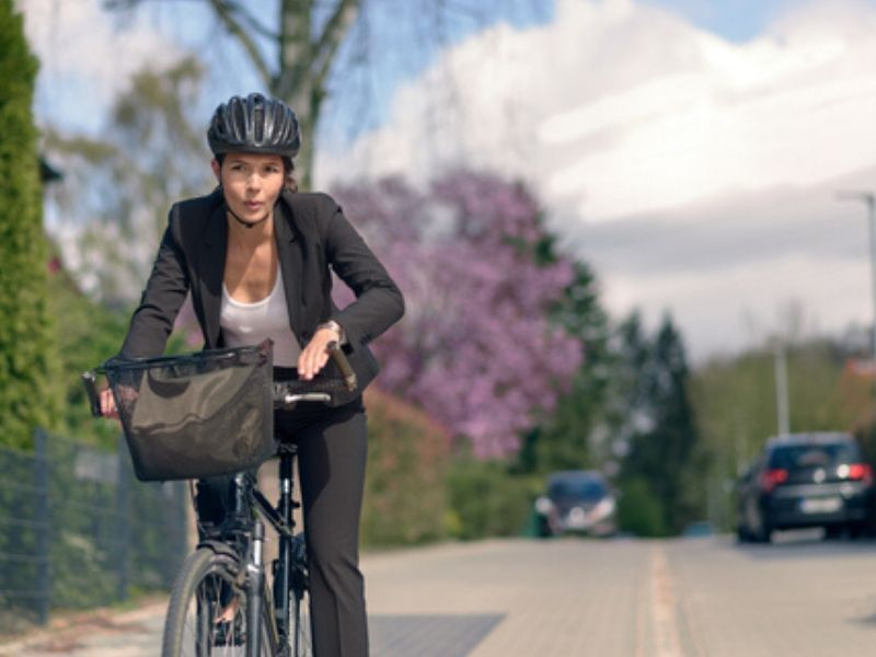 woman in business attire on a commuter bike