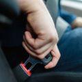 person fastening seatbelt